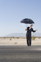 Businessman with umbrella on open road in desert, feeling for rain, low angle view