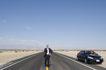 Businessman in middle of open road in desert, using mobile phone by car
