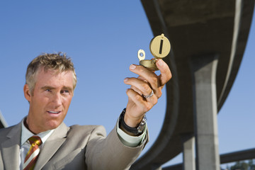 Businessman holding up compass beneath overpass, low angle view