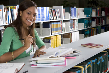 Young woman studying in library, smiling, portrait