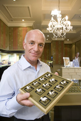 Mature male jewellery shop assistant with tray of rings, smiling, portrait