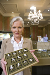 Mature sales woman with tray of jewellery, portrait