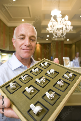 Mature male jewellery shop assistant with tray of rings, smiling