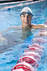 Male swimmer in swimming pool, smiling, portrait, close-up