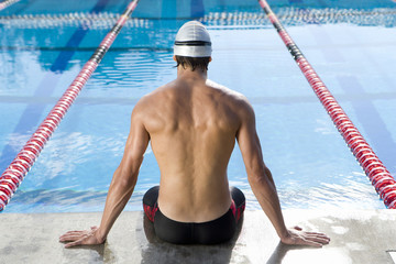 Male swimmer on edge of swimming pool, rear view