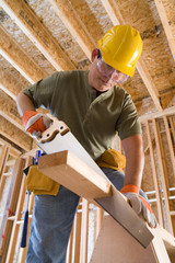 Builder in hardhat sawing, low angle view