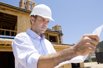 Architect with blueprint in front of partially built house, low angle view