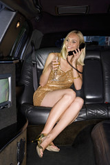 Young woman with champagne flute on telephone in car, smiling