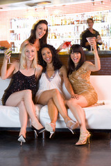 Medium group of young women with drinks in bar, smiling, portrait