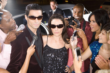Young couple in sunglasses surrounded in paparazzi, close-up