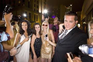 Small group of young women and bodyguard surrounded by paparazzi