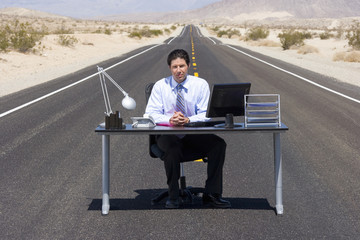 Businessman at desk in middle of road in desert, portrait