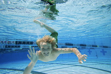 Boy (10-12) in swimming pool, portrait, underwater view