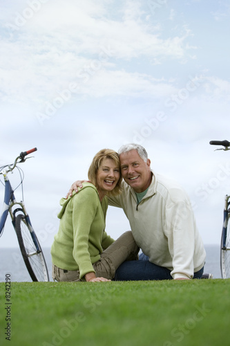 Mature couple arm in arm by sea, on grass with bicycles, smiling, portrait