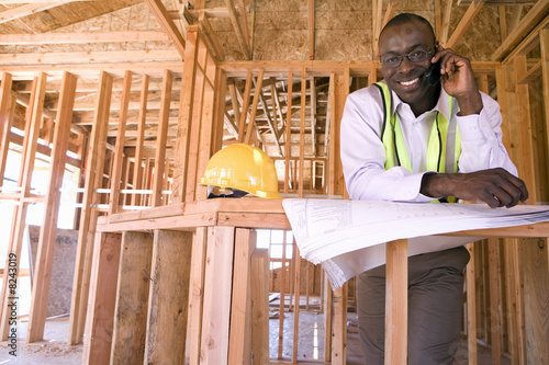 Businessman with blueprints using mobile phone in partially built house, smiling, portrait