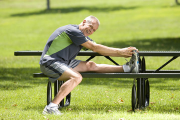 Mature man stretching on park bench, smiling, portrait