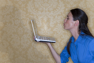 Young woman blowing kiss at laptop computer in hand, profile