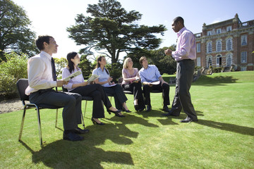 Businessmen and women with folders in training course by manor house