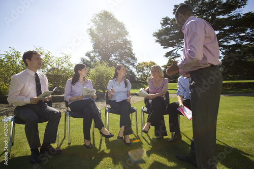 Businessmen and women with folders in training course by manor house (lens flare)
