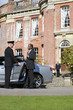Chauffeur holding open door of car for businessman by manor house, low angle view