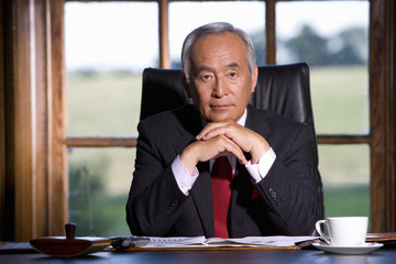 Mature businessman at desk, chin on hands, portrait