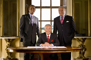 Mature businessman at desk flanked by colleagues, smiling, portrait