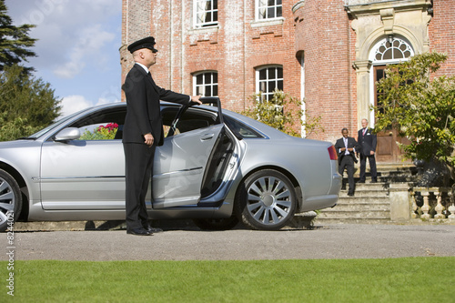 Chauffeur holding open door of car by manor house, businessmen in background