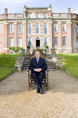 Mature man on chair in grounds of manor house, portrait