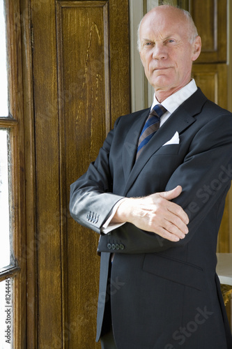 Senior businessman by window, arms crossed
