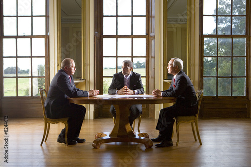 Businessman and colleagues in meeting at table, side view