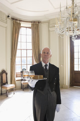 Butler with tray of drinks, portrait