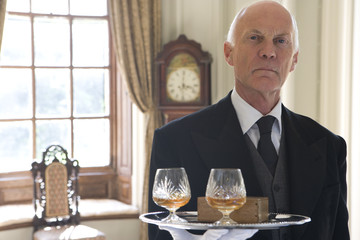 Butler with tray of drinks, portrait, close-up