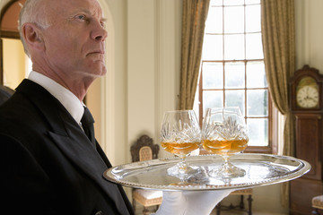 Butler with tray of drinks, low angle view