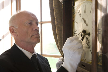 Butler adjusting grandfather clock, close-up