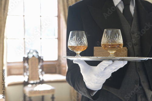 Butler with tray of drinks, mid section