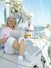 Mature woman with laptop computer on boat, smiling, portrait