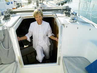 Woman in entrance to cabin of boat, smiling, portrait