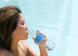 Young woman drinking water from clear plastic bottle