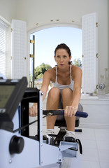 Young woman using exercise machine