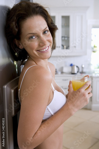 Young woman in underwear with drink in kitchen, smiling, portrait