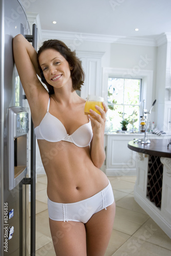 Young woman in underwear with drink in kitchen