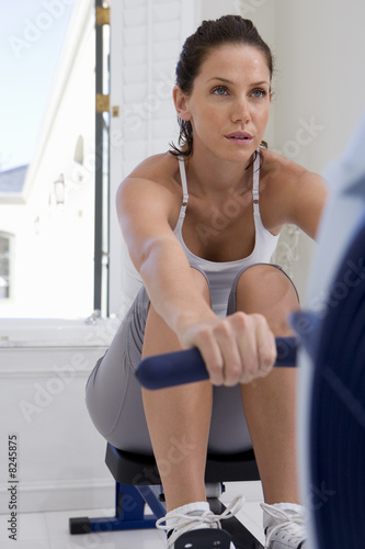 Young woman using exercise machine, low angle view
