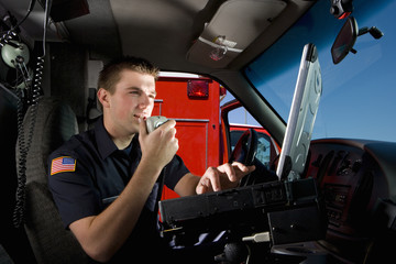 Paramedic in cab of ambulance, using communication equipment, low angle view