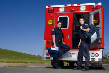 Paramedic and colleague by open door of ambulance, portrait, low angle view