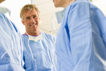 Surgeon smiling at colleague, low angle view
