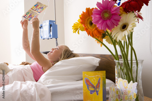 Girl (8-10) in hospital bed reading card, side view