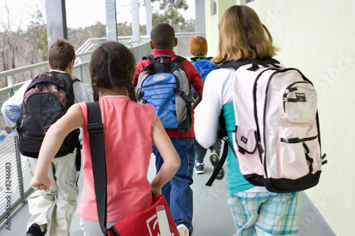 School children (10-12) with rucksacks, rear view