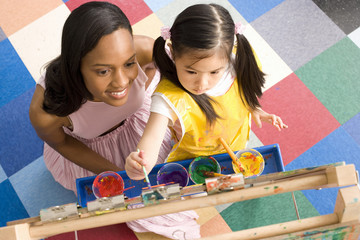 Teacher by girl (5-7) using easel to paint, elevated view