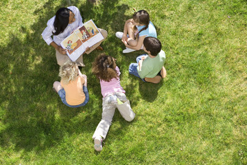 Teacher reading book to children (5-9) outdoors, elevated view
