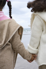 Sisters (5-9) holding hands on beach, rear view